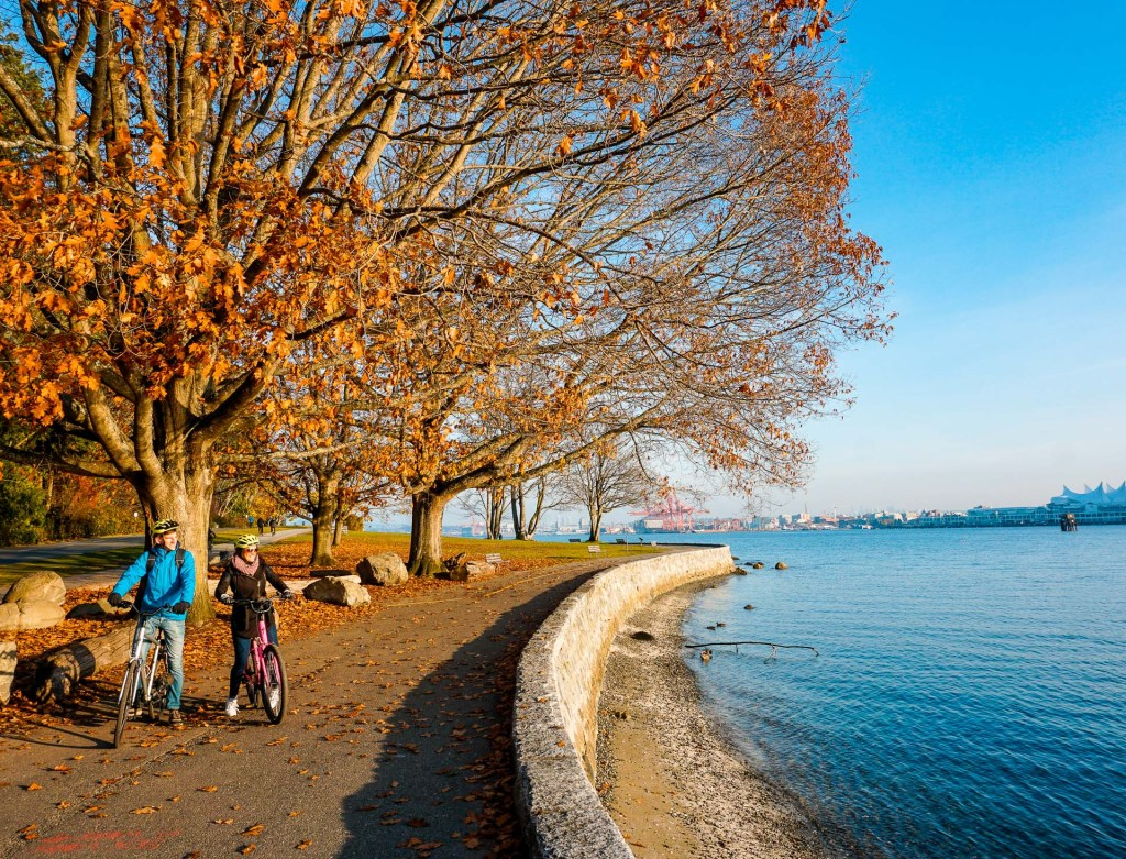A couple biking along Stanley Park's Seawall in Vancouver - an activity you must include in your Vancouver itinerary!