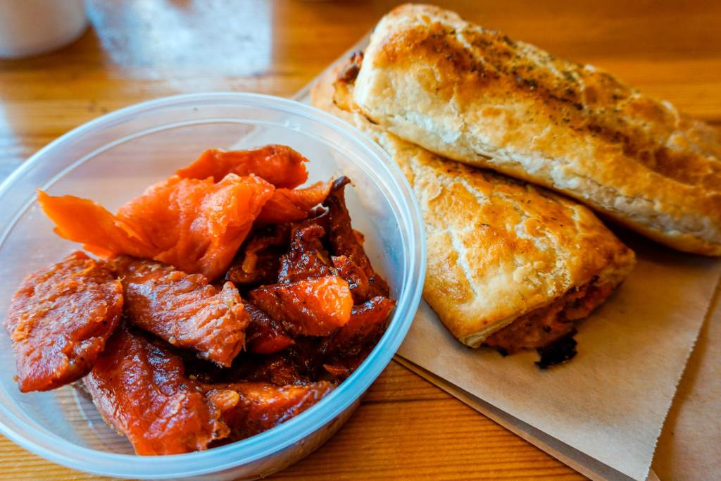 A plastic cup filled with candied salmon and smoked salmon with two salmon puff pastries next to it.