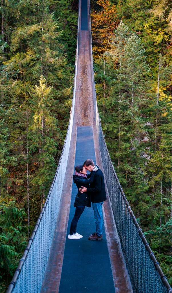 A couple linking together while facing each other in the middle of the Capilano Suspension Bridge in Vancouver.
