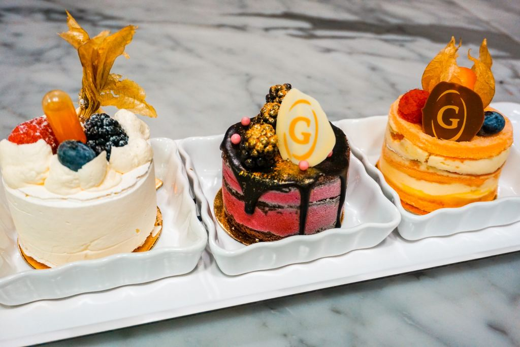 A trio of desserts. The left one is a light white pavlova with fresh berries on top. The middle is a dark pink entremet cake of cassis and chocolate. The right one is orange with stacked cakes of mandarin and mousse. These pastries can be found at Ganache Patisserie in Vancouver.
