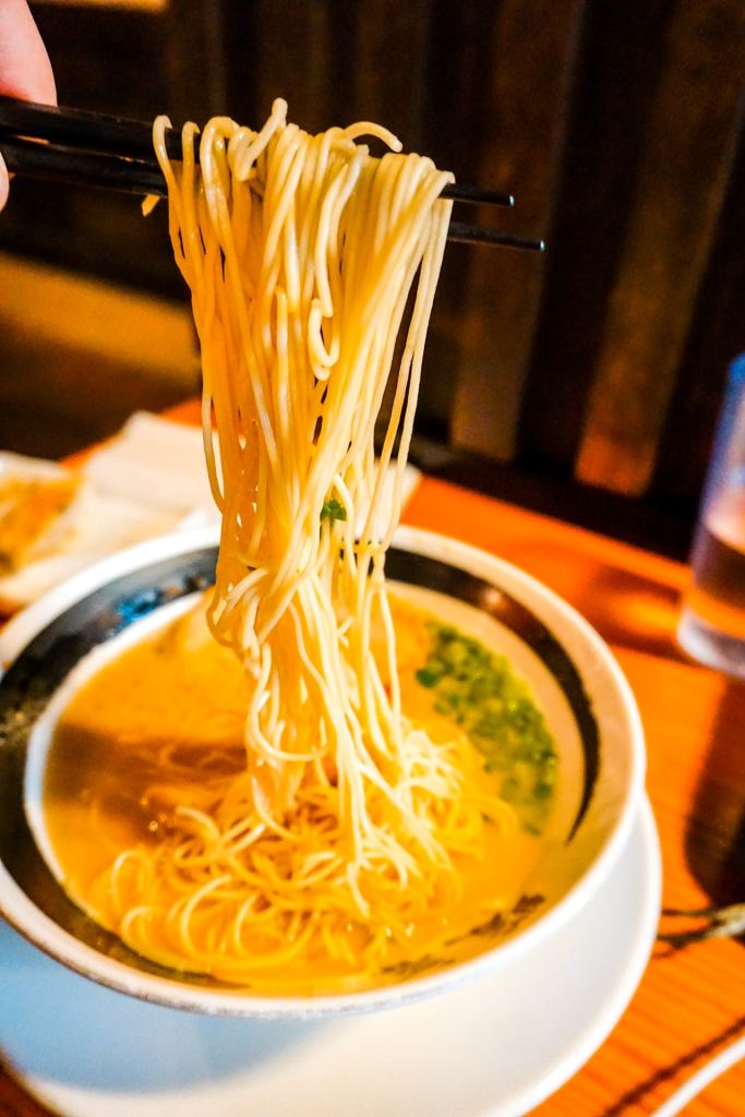 Oodles of noodles being picked up by chop sticks and lingering over a bowl of ramen soup from Ramen Danbo in Vancouver.