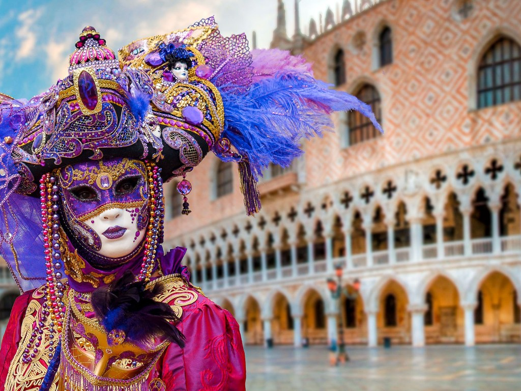 A woman dressed in a purple hat and mask and a fuschia dress for the Carnival of Venice.