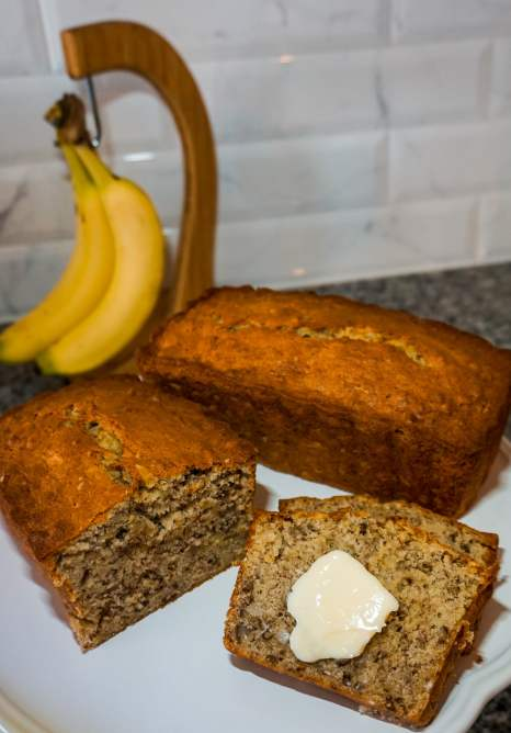 A trio of the best banana nut bread recipe - half a loaf, a full loaf, and two slices with a slab of butter on top.