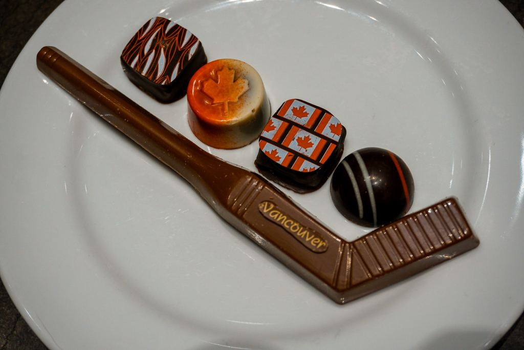 """A plate with four pieces of chocolate and a milk chocolate hockey stick with """"Vancouver"""" on it from ChocolaTas - one of the best places to eat in Vancouver for chocolate."""