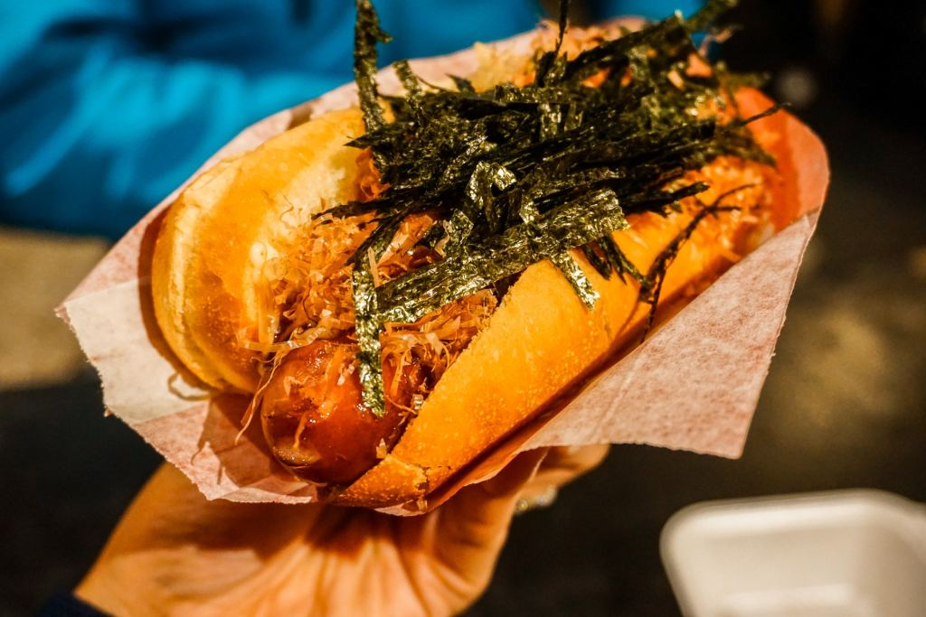 A hand holding a hot dog with seaweed on top. This is a Japanese-style hotdog from Japadog which is one of the best places to eat in Vancouver.