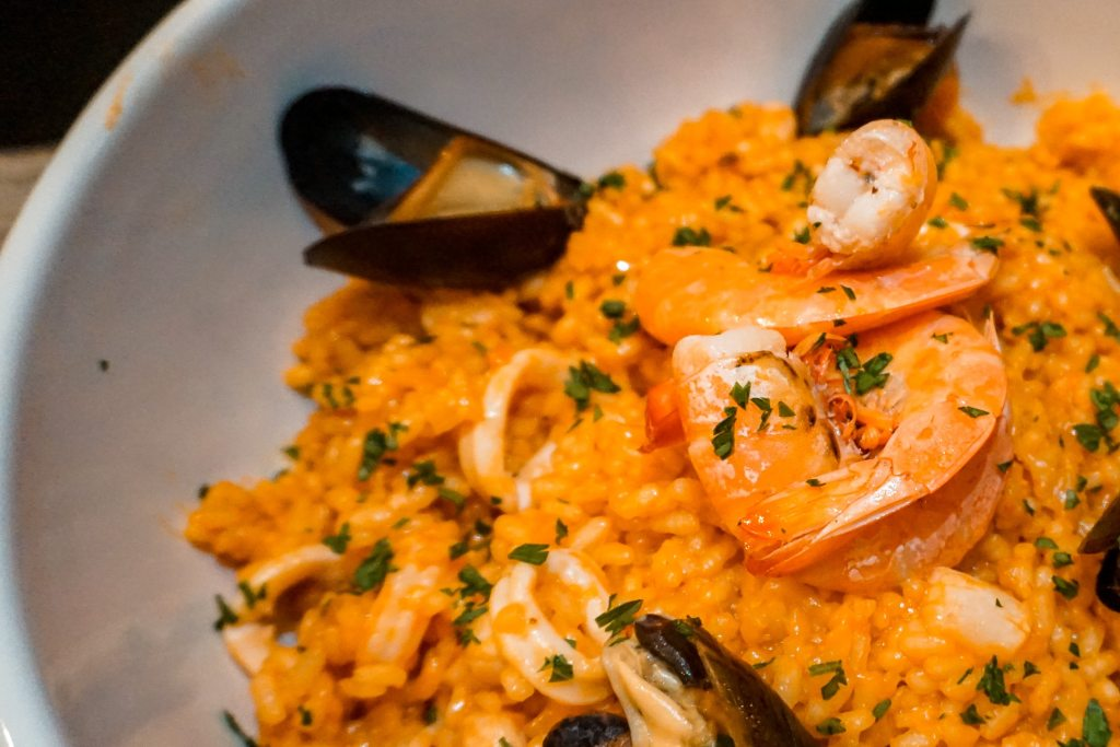 A close up photo of a bowl of seafood risotto.