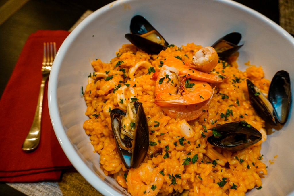 A large bowl of seafood risotto with mussels, prawns, scallops, and calamari. A red cloth napkin is on the left with a fork on top.