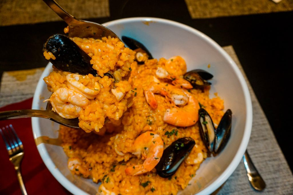 Two spoons serving from a bowl of authentic seafood risotto inspired by Southern Italy.