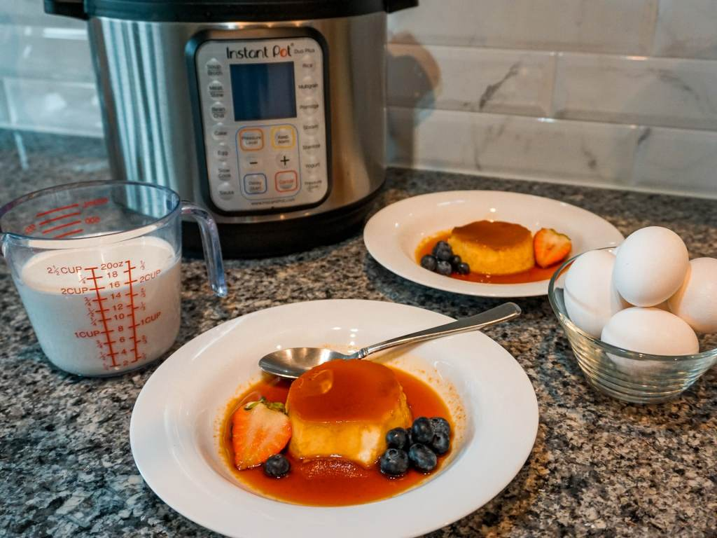 A cup of half and half, bowl of eggs, Instant Pot, and two plates of flan with berries.