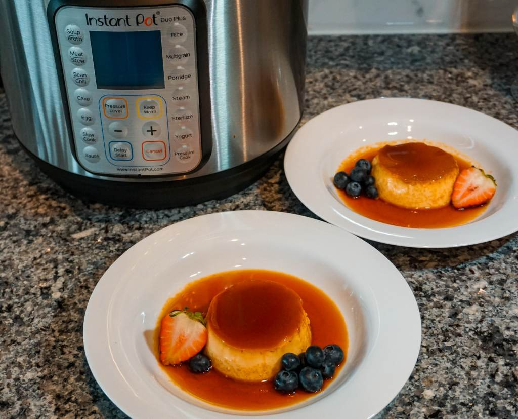 Two plates of flan (creme caramel) with a nice layer of caramel on top and surrounding it. It is served with a strawberry slice and blueberries. Then in the back, is an Instant Pot used to cook the flan.