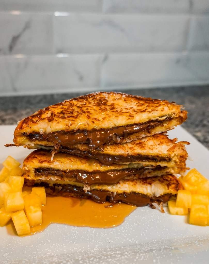 A close up of four triangle slices of Nutella French toast with coconut stacked on top of each other with syrup pouring down and a side of diced pineapple.