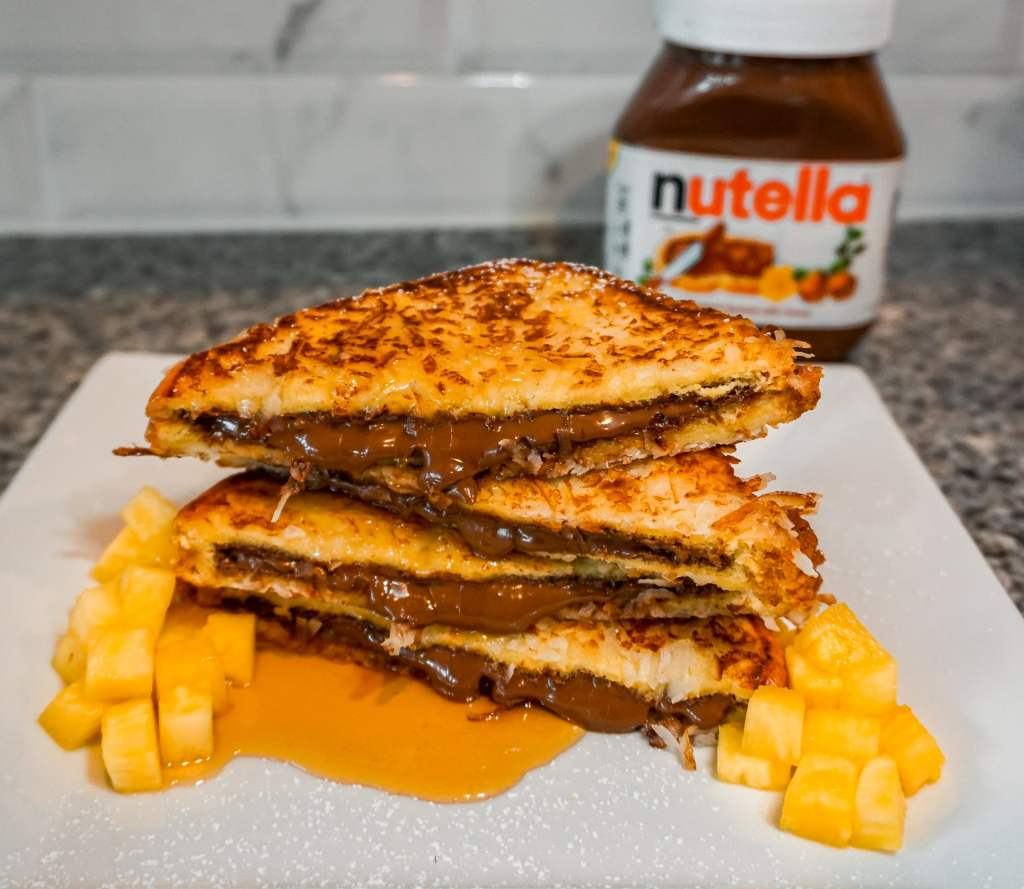 A stack of Nutella filled French toast with a side of pineapple and a jar of Nutella in the background.