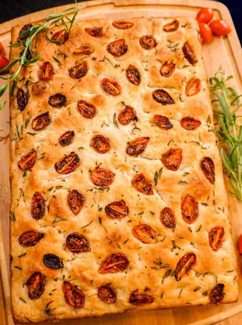 A loaf of roasted cherry tomato and rosemary focaccia bread on a wooden board with fresh rosemary springs and cherry tomatoes surrounding it.