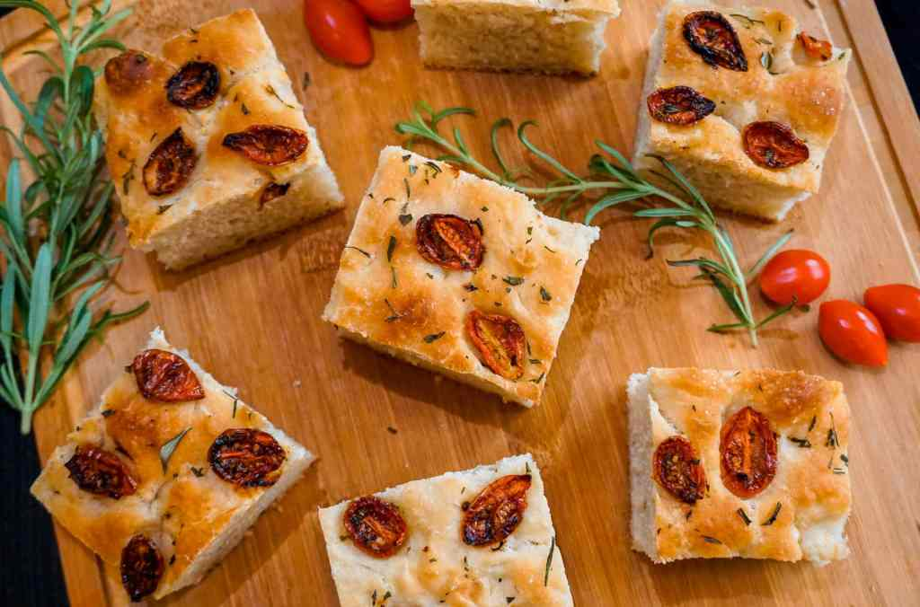 Birdseye view of roasted cherry tomato and rosemary focaccia sliced in squares with springs of rosemary and cherry tomatoes on a wooden board.