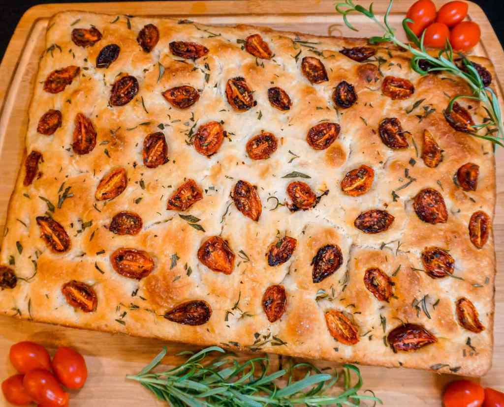 A beautiful loaf of roasted cherry tomato and rosemary focaccia bread on top of a wooden board with fresh rosemary springs and cherry tomatoes.