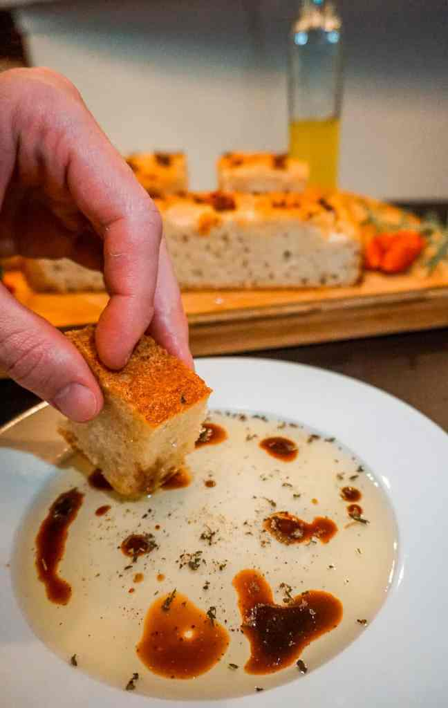 A close up of someone dipping a piece of focaccia into a plate of olive oil and balsamic vinegar.
