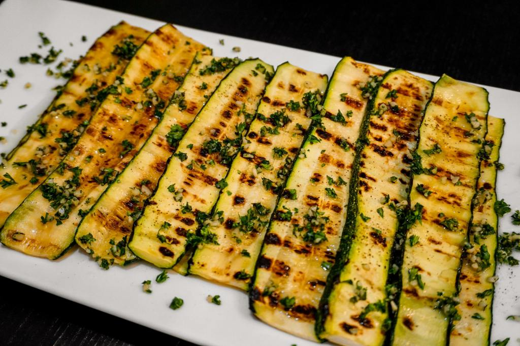 A rectangle plate full of Italian style grilled zucchini layered on top of each other.