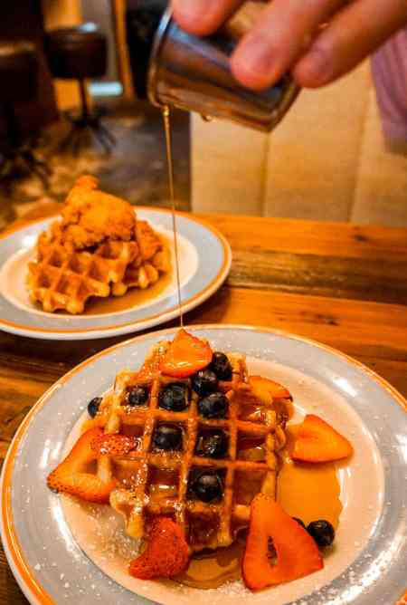 A man pouring maple syrup over Belgian waffles with fresh blueberries and strawberries from Layered in McKinney, Texas.