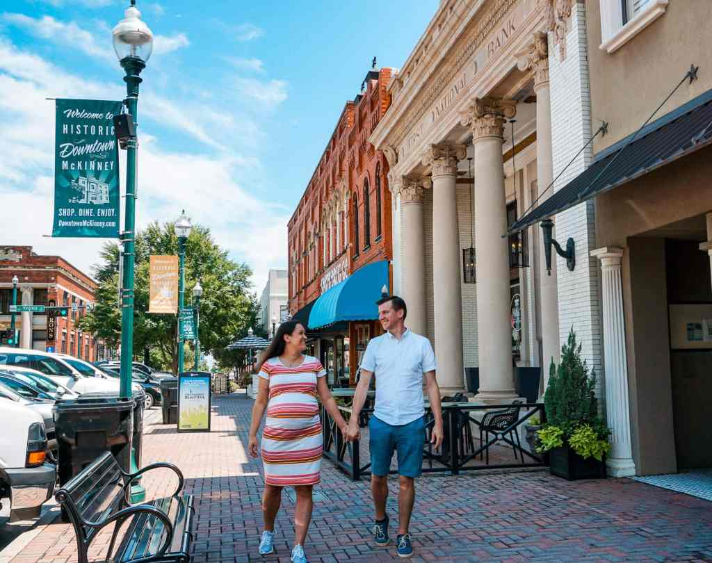An expecting couple walking in historic downtown McKinney, Texas, one of the best babymoon destinations around the world.