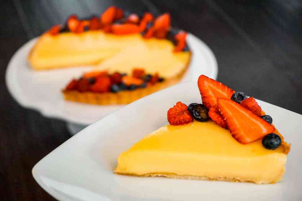 A slice of French Lemon Tart (Tarte au Citron) with fresh berries in focus with the whole tart in the background.