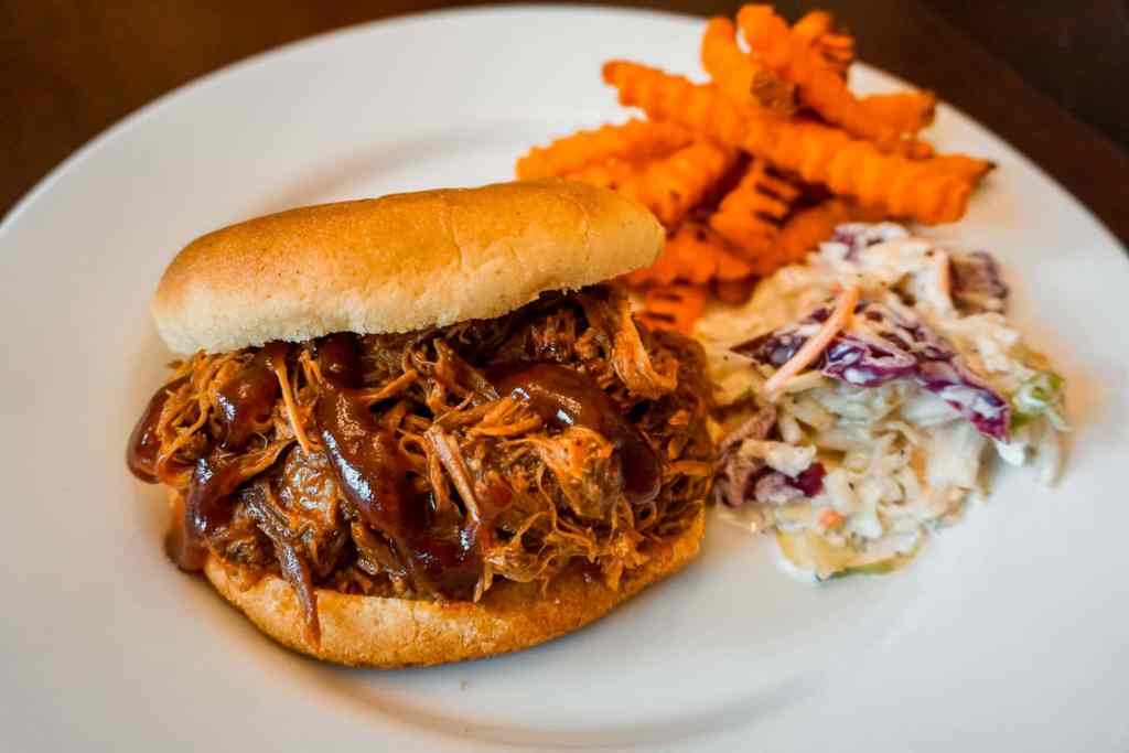 A plate of Texas pulled pork sandwich with a side of coleslaw and sweet potato fries.