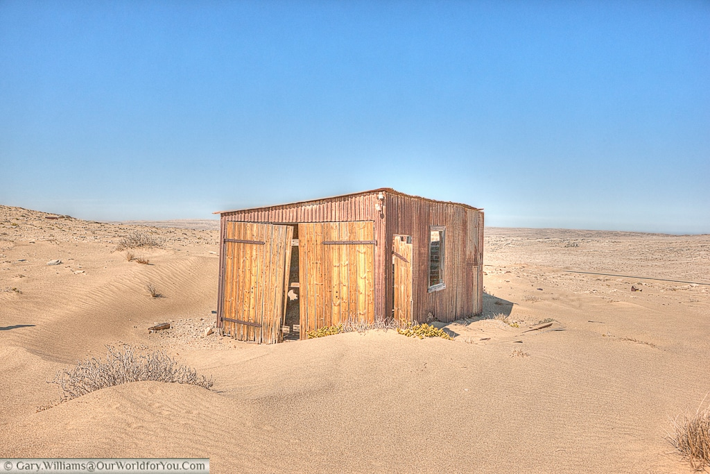 A small hut on the outskirts of town stands abandoned, Kolmanskop, Namibia