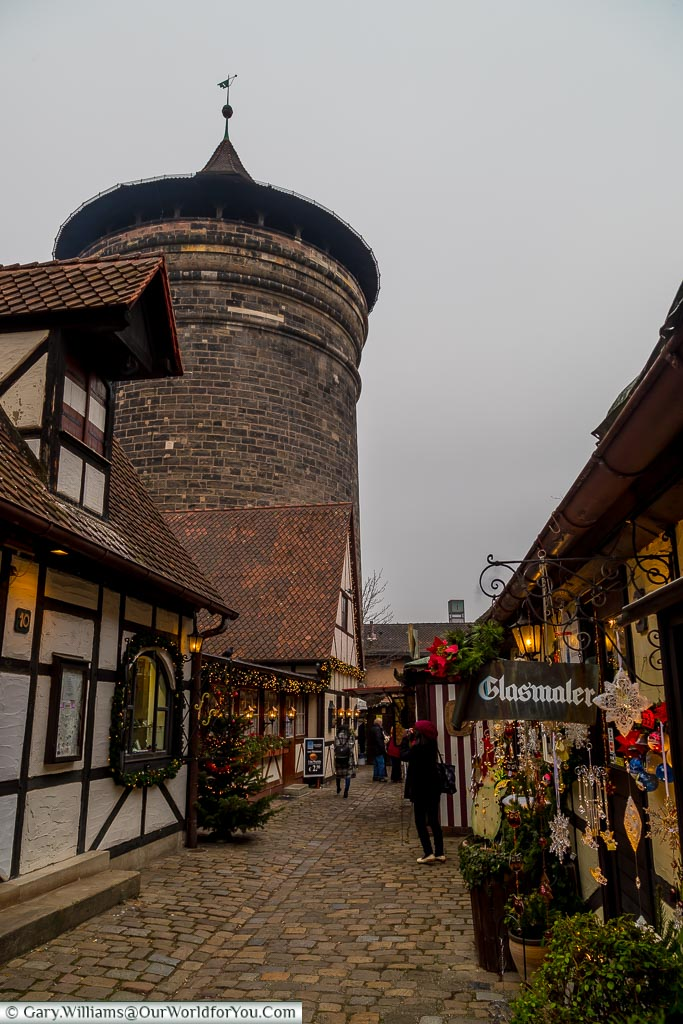 Looking along a cobbled lane within Nuremberg's Craftsmen courtyard with one of the cities medieval towers in the background.