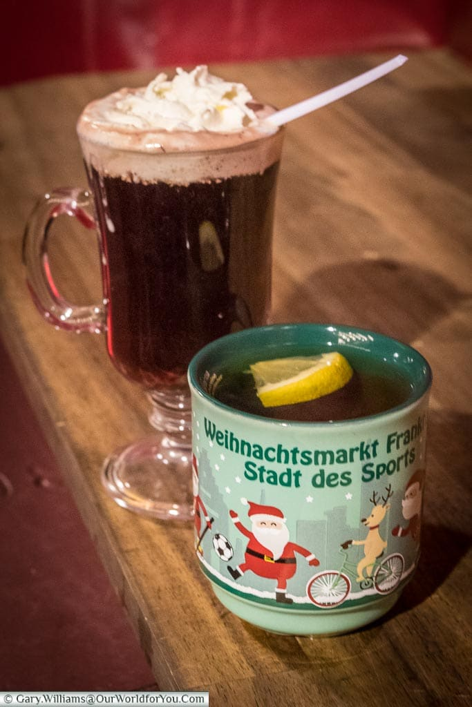 Two drinks from the Frankfurt's Christmas markets.  The first is a mug of Frankfurt's speciality apple gluhwein; the other is a glass Irish-Coffee style glass with a cherry gluhwein, topped with cream.
