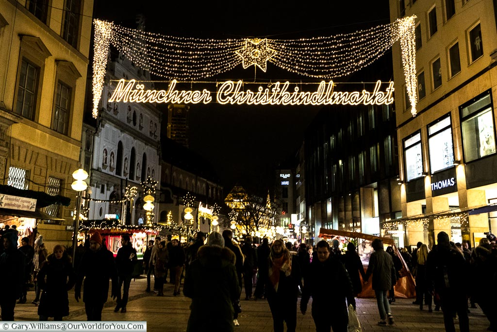 Pedestrians are walking along one of Munich shopping streets at night under fairy light telling you you are entering 'Müchner Christkindlmarkt.'