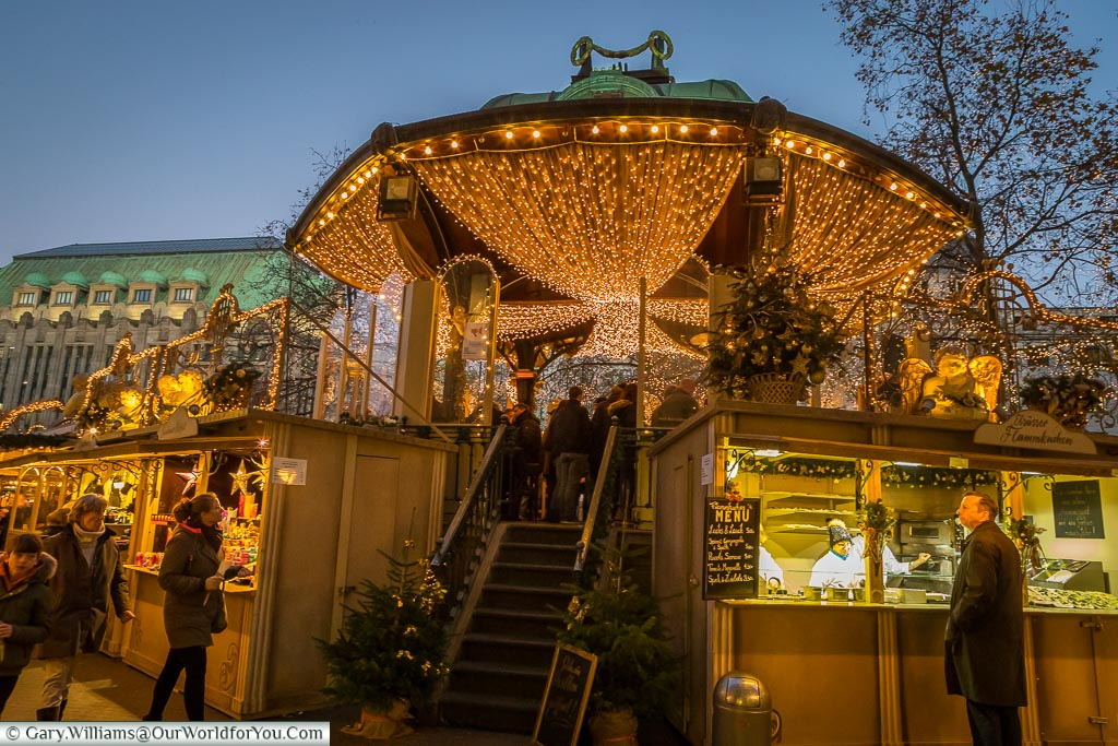 Market stalls either side of the steps up ornate bandstand decorated with curtains of golden fairy lights.