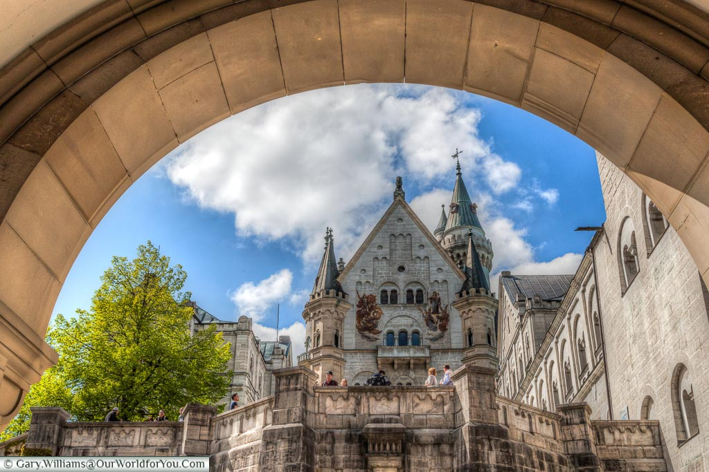 The view through the gateway of Schloss Neuschwanstein into the inner courtyard looking up at the towers and main entrance with blue skies and light coulds.