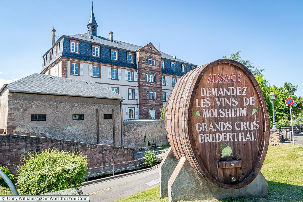 A large oak wine barrel in front of a grand building.  The writing on the oak barrel states 'demand the wines of Molsheim' - in French of course.