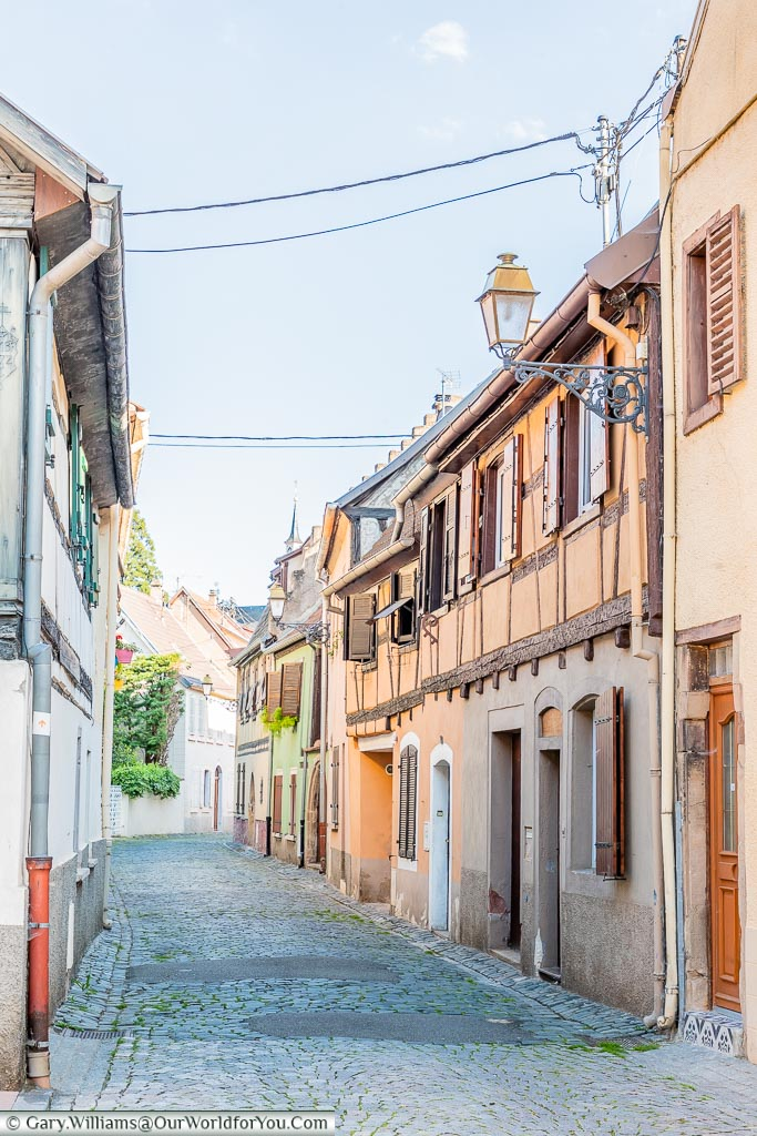 Looking down a cobbled lane of half-timbered houses typical of the region.