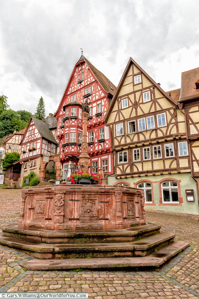 A red stone fountain, against the backdrop of the half-timbered houses of the Alter Marktplatz in Miltenberg