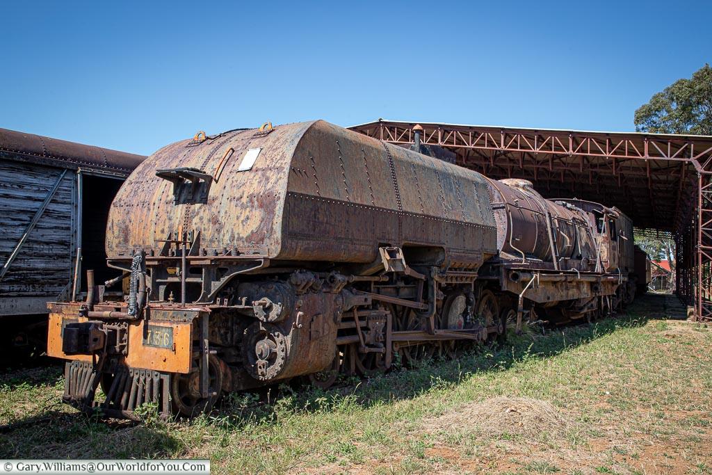A massive Garratt steam locomotive, extensively rusted.