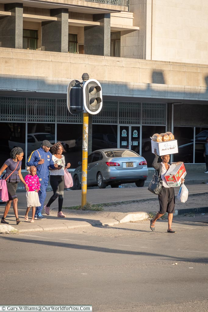 A woman is crossing the road with a large box in one hand and another on her head, with three loaves of bread on top of that too.