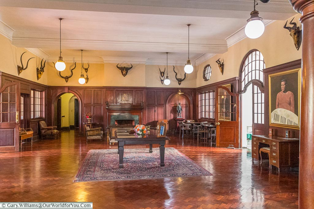 The wooden panelled reception area of the Bulawayo club in a colonial style with mounted antelope heads adorning the upper part of the walls.