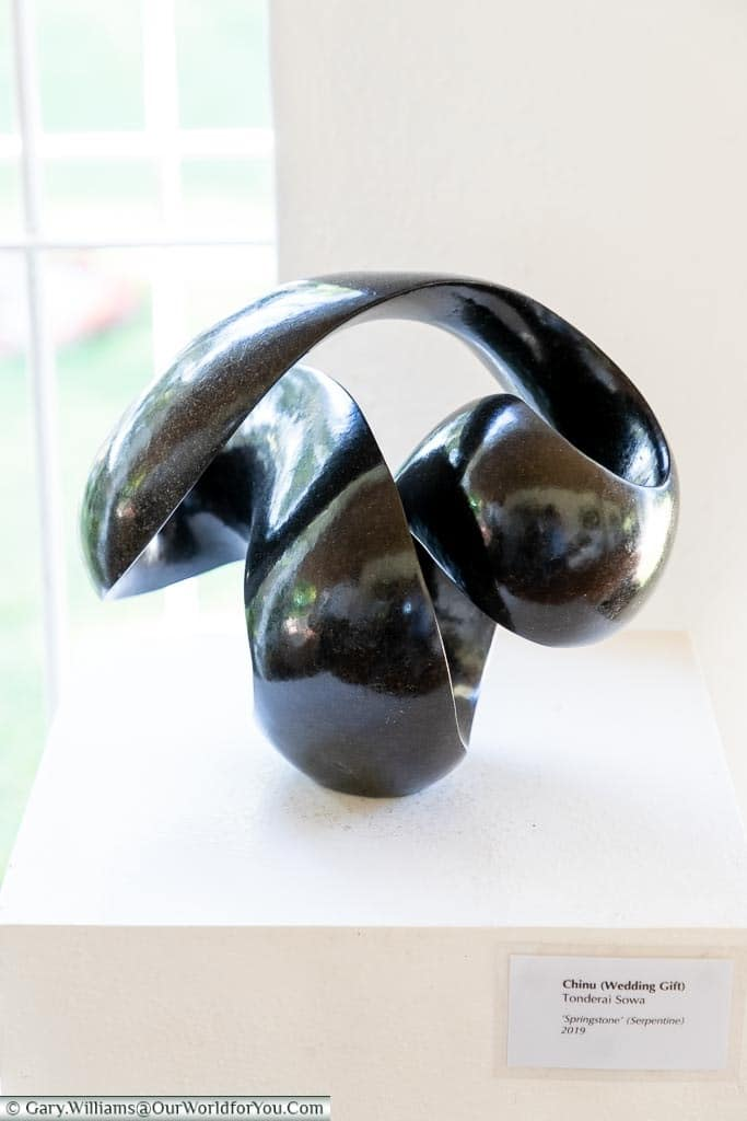 """A carved stone piece of a looped ribbon entitled """"Wedding Gift"""" by Tonderai Sowa."""