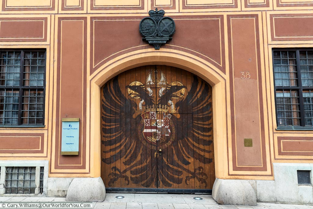 A pair of large wooden gates, decorated with a twin-headed eagle and a heraldic shield that mark the entrance to the Fürst Fugger Privatbank.