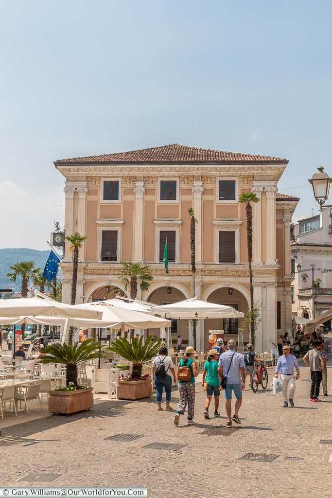 An elegant building on the edge of a piazza with a group of a people walking along the street in front of it.