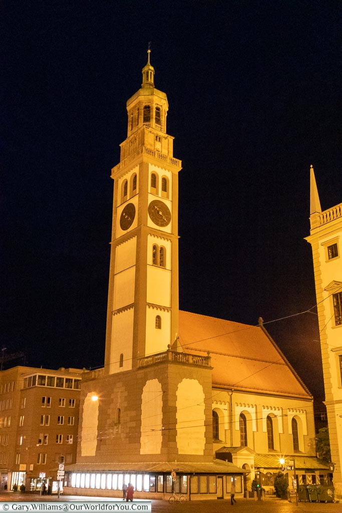 A tall bell tower, illuminated against the night sky, known as the Perlachturm.