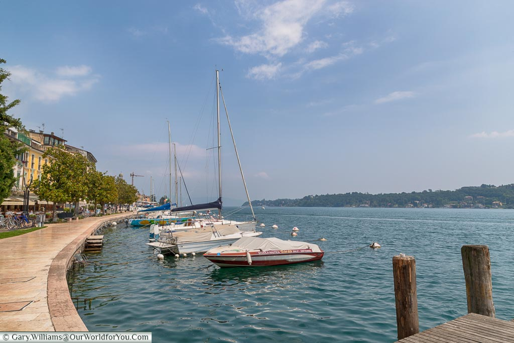 A lakeside view with small boats moored up alongside the promenade at Salò.