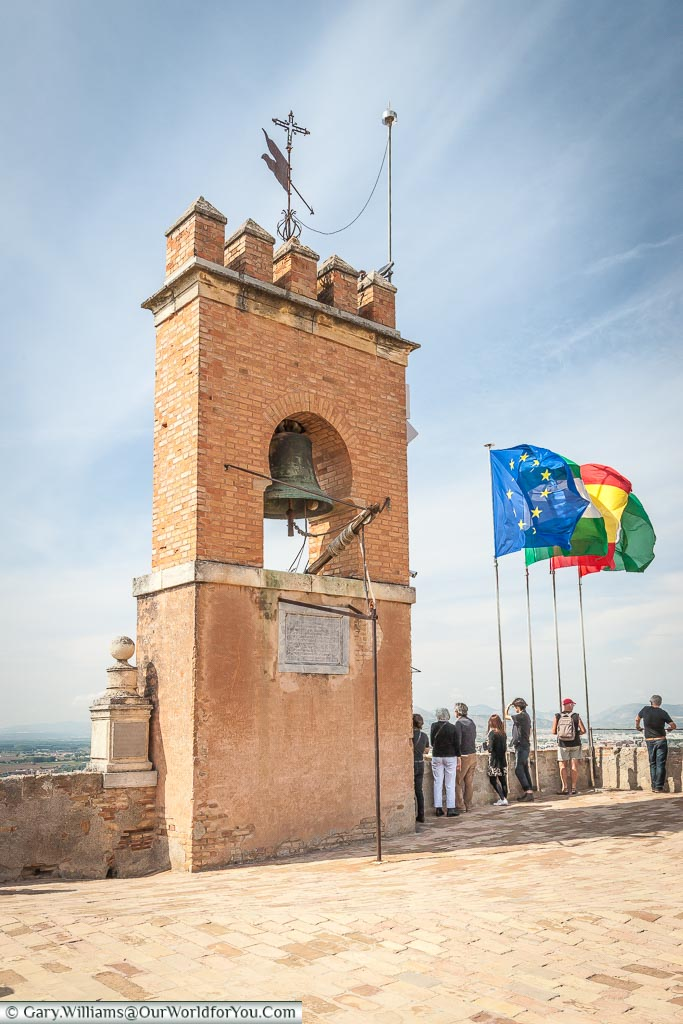 The bell tower at the top of the Alhambra palace with flags fluttering in the breeze.