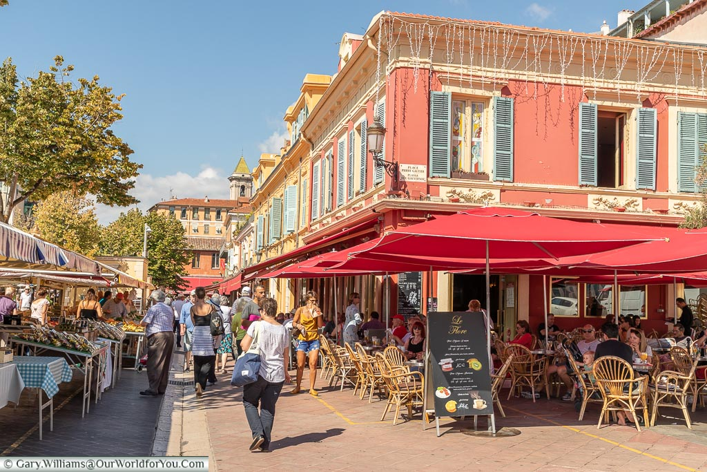 A street scene of a café next to the fruit & vegetable market with people sitting at a bunch of tables under bright red canopies.