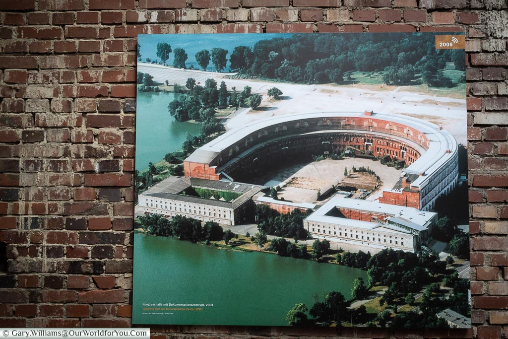 An aerial photo of the congress building from 2001 mounted on a wall inside the documentation centre.