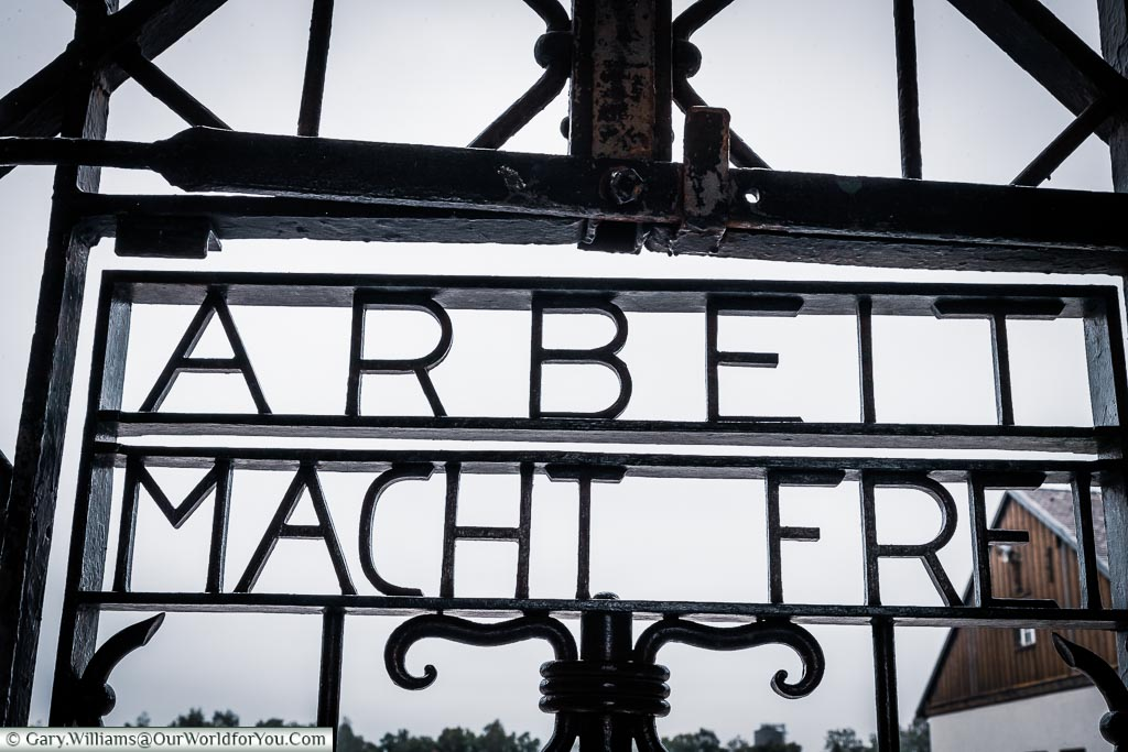 The motto 'Arbeit macht frei' which translates to 'Work Sets You Free' set in wrought iron in the gate to the entrance to the camp.