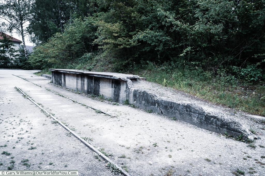 The railroad tracks in front of a crumbling platform that was once the disembarkation point of prisoners to the camp.