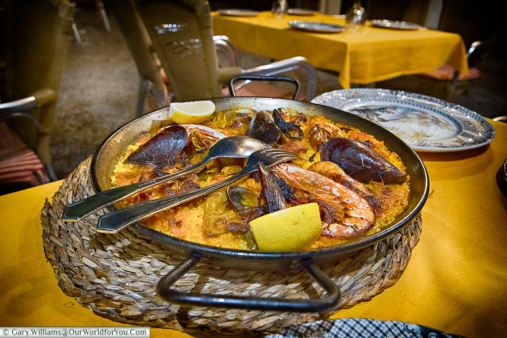 A large iron pan of saffron-coloured paella with mussels and giant prawns to share.