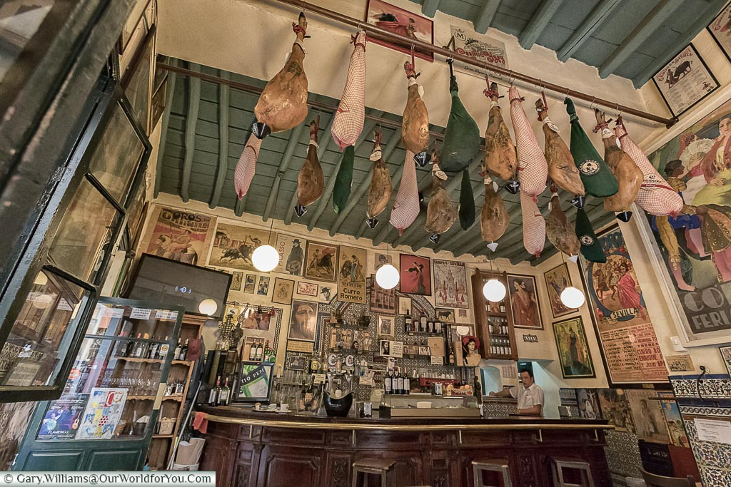 The counter of Casa Placido, a traditional bar with hams hanging from the roof.