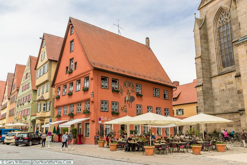 Tables and chairs under parasols in front of the colourful Café am Münster.  The picturesque buildings are painted in traditional colours, the cafe supporting a historic looking mural.